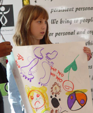 little girl showing a poster drawing